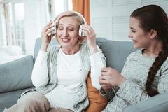 Begeisterte positive Greisin, die ihre Kopfhörer hält stockfotos