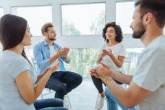 Begeisterte positive Gruppenmitglieder, die sich stützen Lizenzfreies Stockfoto
