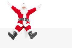 Begeisterte Santa Claus, die auf einer Leerplatte sitzt Stockfotografie