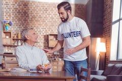 Begeisterter älterer Mann, der Freiwilligen betrachtet stockfotos