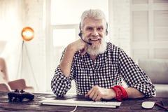 Begeisterter älterer Mann, der an seinem Arbeitsplatz sitzt lizenzfreie stockfotos