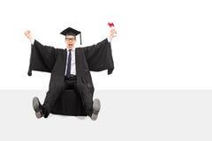 Begeisterter Absolvent, der ein Diplom hält Stockbild