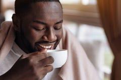 Begeisterter Afroamerikanermann, der die Tasse Tee genießt Stockfotos