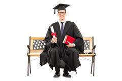 Begeisterter Collegeabsolvent, der auf einer Bank sitzt Stockbild