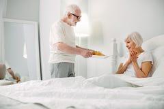Begeisterter gealterter Mann, der für seine Frau sich interessiert Stockbild