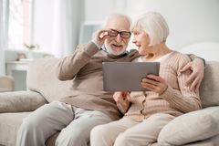 Begeisterter gealterter Mann, der seine Gläser repariert lizenzfreies stockbild