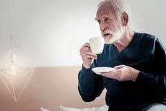 Begeisterter gealterter Mann, der seinen Tee genießt stockfotos