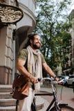 Begeisterter glücklicher Mann, der sein Fahrrad verwendet Stockfotos