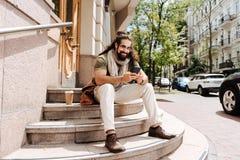 Begeisterter gutaussehender Mann, der eine Mitteilung schreibt Stockfoto