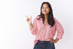 Begeisterter junger Asiat weiblich in gestreifter Blusenholdinghand auf der H?fte froh und, die stolz als Zeigen auf oberes smirk lizenzfreie stockfotografie
