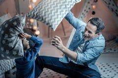 Begeisterter junger Mann, der mit Kissen kämpft lizenzfreie stockbilder