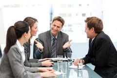 Begeisterter Manager, der mit seinem Team an einem Tisch spricht Stockfotos