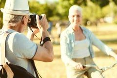 Begeisterter netter Mann, der eine Kamera hält lizenzfreie stockfotografie