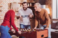 Begeisterter Pensionär, der ein Spiel mit seiner Frau spielt stockbilder