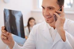 Begeisterter positiver Doktor, der am Telefon spricht stockbild