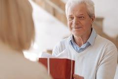 Begeisterter positiver Mann, der ein Geschenk gibt stockfoto