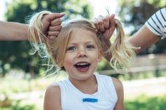 Begeistertes Kind mit netten Pferdeschwänzen Zeit draußen verbringend lizenzfreies stockfoto