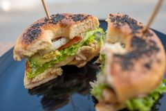 Begel black sesame with chicken salad cut in half with stick on top. Begel black sesame with chicken salad cut in half with stick on top in black plate stock image