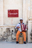 Beggar - Accordionist. A beggar playing the accordion and begging in front of a church stock photography