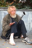 Beggar beg passers. MOSSOW, RUSSIA - OCTOBER 1, 2012: Homeless man sitting on the pavement with a bandaged leg and begging passers on October 1, 2012 in Moscow Royalty Free Stock Photography
