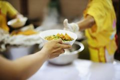 Beggar begs food from donors: concept of poverty in Asian society.  stock photo