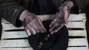 The beggar considers coins. A beggar on the street is holding dirty hands with money stock footage