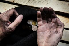 The beggar considers coins. stock image