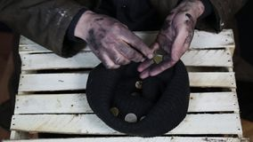 The beggar considers coins. A beggar on the street is holding dirty hands with money stock video footage