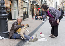 Beggar with dog Stock Image