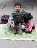 Beggar with dogs on the ground Royalty Free Stock Images