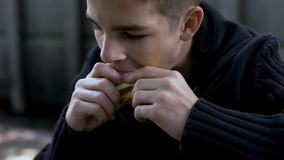 Beggar eating sandwich on street, social help for people in need, orphan child. Stock photo stock images