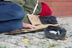 Beggar falling asleep on the street Stock Images
