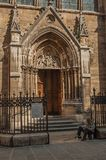 Beggar in front of gothic church on an alley at sunset in Paris. Paris, France - July 08, 2017. Beggar in front of gothic church on an alley at sunset in Paris Stock Images