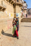 Beggar on the ghats of Varanasi. A beggar with her child is walking along on the holy ghats of the ancient hindu city of Varanasi Stock Image