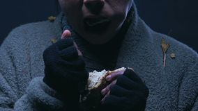 Beggar greedily eating bread, poverty and starvation problem, worldwide hunger. Stock footage stock footage