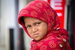 Beggar indian girl begs for money from a passerby in Srinagar, Kashmir. India. SRINAGAR, INDIA - JUNE 10, 2015: Unidentified beggar girl begs for money from a Royalty Free Stock Photos