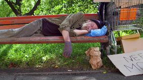 Beggar on lying on bench, hat with coins and board with sign need money on ground. Life of lonely old homeless man stock video footage