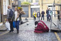 A beggar man with a glass in his hand asks for alms. Crowd pass by. LONDON, ENGLAND - October 12, 2018 A beggar man with a glass in his hand asks for alms. Crowd stock photography