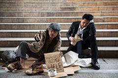 Beggar old man and drunk Businessman in town. Portrait of old beggar or homeless senior guy raise hand to ask for money while drunk Business men or Buinessman Stock Photo