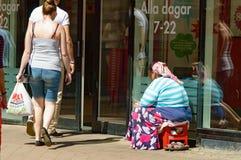 Beggar outside a shop Stock Photos