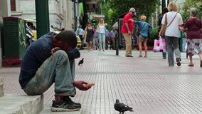 Beggar and people on the street in Athens, Greece stock video