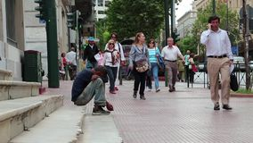 Beggar and people on the street in Athens, Greece stock footage