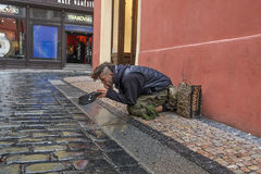 Beggar. In the streets of the Old Town in Prague waiting for a donation from the thousands of tourists crossing this street every day royalty free stock images