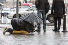 Beggar in the rain with umbrella legs Stock Image