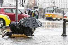 Beggar in the rain with umbrella traffic. Homeless beggar is begging for money in a main street in Sofia holding an umbrella in a rainy day. Bulgaria is the Stock Photos
