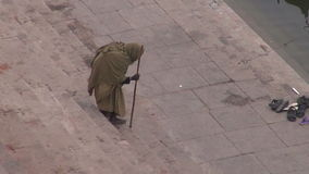 Beggar on sacred Ganges river ghats in Varanasi, India stock footage