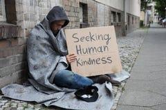 Beggar Showing Seeking Human Kindness Sign On Cardboard. Male Beggar In Hood Showing Seeking Human Kindness Sign On Cardboard royalty free stock photo