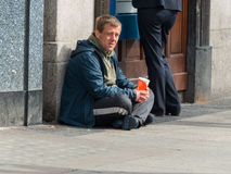 A beggar sits beneath a cash point in O`Connell Street in Dublin Ireland looking for a Euro or two to see him through the day Royalty Free Stock Photography