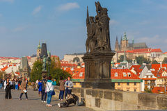 Beggar and tourists on the Charles Bridge in Prague Royalty Free Stock Images