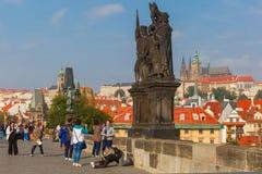 Beggar and tourists on the Charles Bridge in Prague. Prague, Czech Republic - October 6, 2014: Beggar, homeless kneeling begging on the Charles Bridge and royalty free stock images